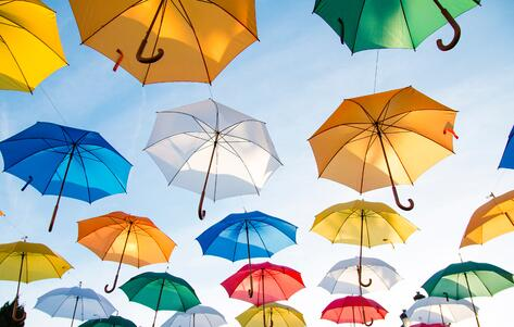 Several umbrellas that are all different colors hanging in the sky