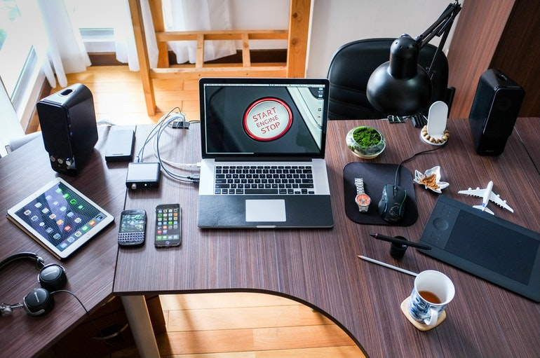 computer desk with headphones, iphone, ipad, coffee in a mugand laptop