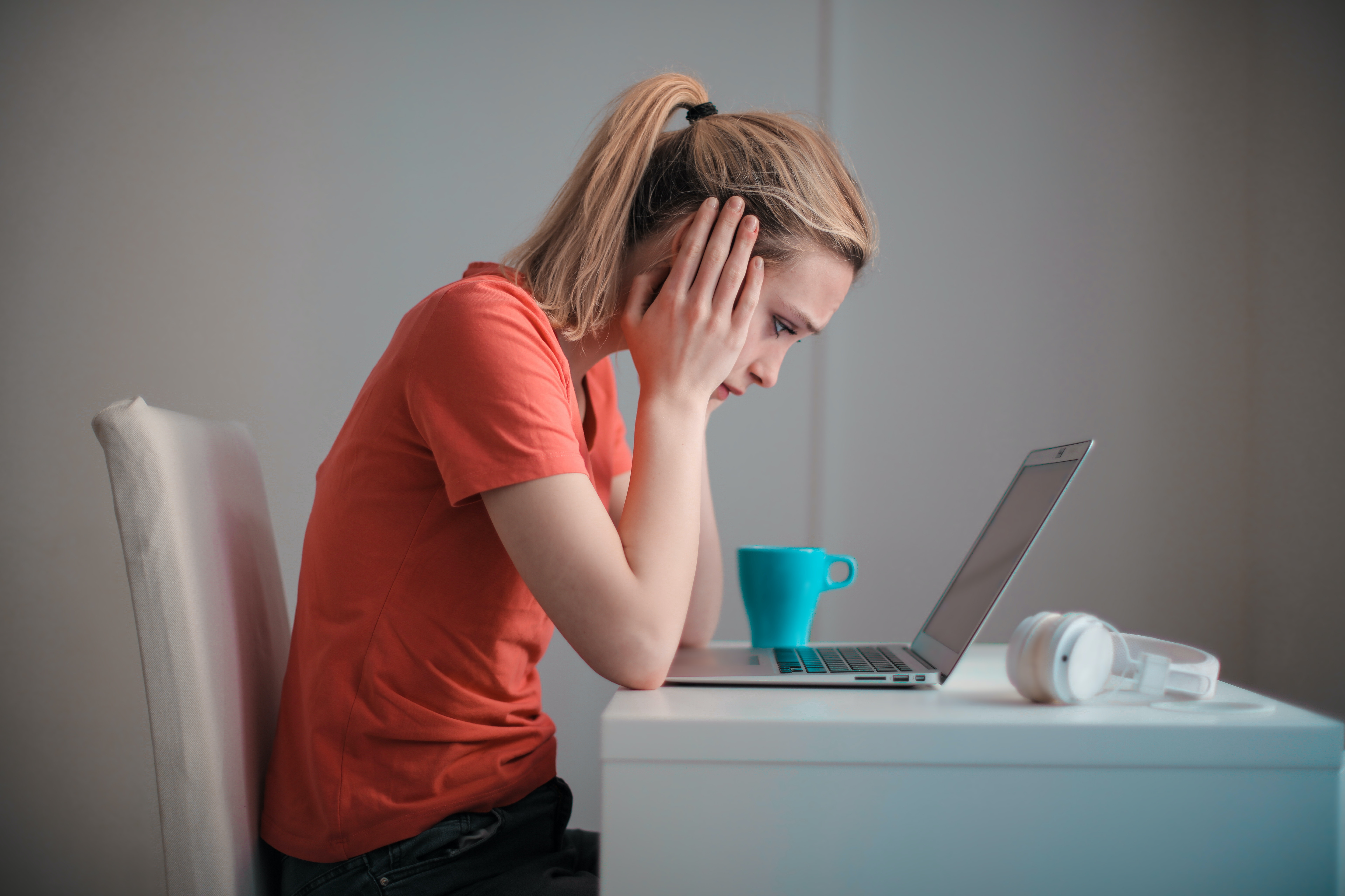 Stressed woman looking at laptop at her desk with mug and headphones
